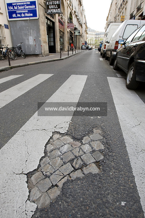 Paving stones are visible through a whole in the road's asphalt in the Quartier Latin neighborhood of Paris, France, 2 May 2008. During the May 1968 riots paving stones were used as projectiles against the police.