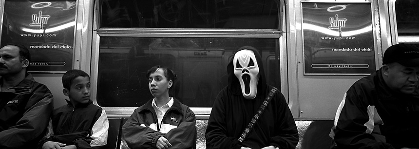 """A subway rider wears a mask from """"Scream"""" on Halloween. Subway series shot in New York between the years 1998 and 2001"""