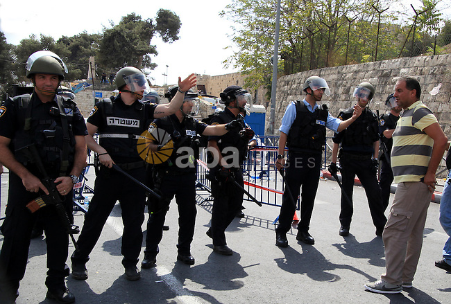 A Palestinian man argues with Israeli policemen as they stand guard outside Jerusalem's Old City Friday, Oct. 9, 2015. At least four attacks, three by Palestinians and one by an Israeli, as well as deadly clashes along the Gaza border threatened to escalate tensions throughout the country on Friday as Israel struggled to control spiraling violence. Photo by Mahfouz Abu Turk