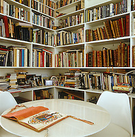 In the library a Tulip table and matching chairs by Eero Saarinen are surrounded by walls lined with antique and modern books