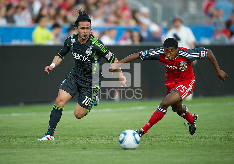 Seattle Sounders FC midfielder Mauro Rosales #10 and Toronto FC defender Danleigh Borman #25 in action  during an MLS game between the Seattle Sounders FC and the Toronto FC at BMO Field in Toronto on June 18, 2011..The Seattle Sounders FC won 1-0.