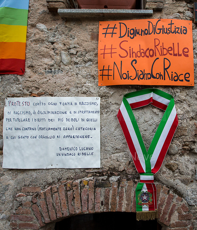 """Tricolor band, symbol of the Mayor, pin up on a wall.<br /> <br /> Riace (Calabria, Italy), 04/08/2018. Visiting Riace for the third day of the """"Riace in Festival"""", 'Festival delle Migrazioni e delle Culture Locali' (Festival of Migration and Local Cultures). Attending the festival, amongst others, were the Mayor of Napoli Luigi De Magistris and the Mayor of Barcelona Ada Colau, debating with the Mayor of Riace, Domenico 'Mimmo' Lucano, about the so called """"migration crisis"""", as well as the now famous """"Modello Riace"""" (The Riace Model: how to welcome and work with Migrants to invest in building a future together). Other speakers included: Tiziana Barillà, Journalist at """"il Salto"""" (1) and Author of the book """"Mimi Capatosta. Mimmo Lucano e il modello Riace"""" (2),  Magistrates Riccardo De Vito and Emilio Sirianni (in turn President and Member of Magistratura Democratica). Chair of the event was Ilaria Bonaccorsi, Historian & Journalist at """"il Salto"""".<br /> From the Festival website: """"RIACE in FESTIVAL, is an event born in the wake of the policy of reception and resettlement of refugees and asylum seekers that the city administration of the """"Riace Bronzes'"""" town has been implementing for years. [...] The festival aims to be a concrete initiative that, through the universal language of cinema and the arts, promotes the exchange and mutual knowledge to counteract forms of closure and racism, drawing attention to the innovative path that the municipal administration of Riace has started by combining the reception of migrants with the revival of its territory and giving the image of an unpublished Calabria, different from that of the black chronicle>>.<br /> Riace is a small village in the province of Reggio Calabria. It's famous because on the 16 August 1972 Stefano Mariottini, a chemist from Rome, found two full-size Greek bronzes... (Riace Bronzes: https://bit.ly/2oBoFNY)<br /> (For the full caption read the ARTICLE at the the beginning of this story)"""