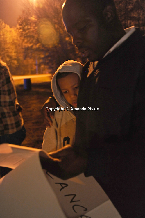 "Desmond Lane, 11, with his father, Darick Lane, 38, of Richmond, Virginia, opponents of the death penalty, during a prayer vigil near the entrance to the Greensville Correctional Center in Jarratt, Va. hours before the 9 p.m. execution of John Allen Muhammad, the so-called ""Washington sniper"" responsible for gunning down 10 and wounding three in the D.C.-area in 2002, on November 10, 2009.  Gov. Tim Kaine refused to grant a stay of clemency and the U.S. Supreme Court turned down the request for a stay of execution despite religious objections due to Muhammad's mental health."