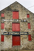 Ireland. Deserted old building with red shutters Drink Football Special sign. Swilly bottlin...