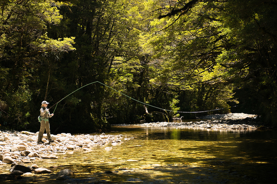 A fly fisher casts to a brown trout in New Zealand's Southern Alps.