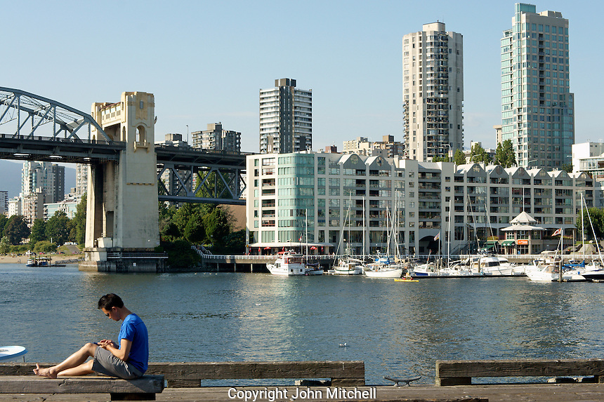 Young Asian man texting on a pier, Granville Island, Vancouver, BC, Canada