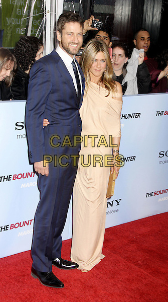 GERARD BUTLER & JENNIFER ANISTON .'The Bounty Hunter' New York Premiere held at the Ziegfeld Theatre, New York , NY, USA, 16th March 2010..arrivals full length navy blue tie suit white shirt beige grecian jersey dress off the cut out shoulder arm around beard facial hair  gold bracelet clutch bag long maxi .CAP/ADM/AC.©Alex Cole/AdMedia/Capital Pictures.