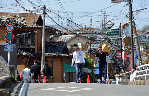 April 17, 2016, Kumamoto, Japan - Local residents carry cardboard boxes containing bottles of water before collapsed houses at Mashiki town in Kumamoto prefecture on Sunday, April 17, 2016. More than 40 people died and some 1,000 injured as massive earthquakes attacked Japan's southern island of Kyushu. (Photo by Yoshio Tsunoda/AFLO) LWX -ytd-