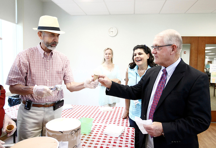 Middlebury, CT- 07 August 2014-080714CM09-  Ron Clark of Middlebury serves an ice cream cone to Middlebury First Selectman, Edward B. St. John at the Middlebury Public Library on Thursday. Looking on is director of the library, Jo-Ann LoRusso, right, and librarian Karen Paskternak  The library held the ice cream social to celebrate the end of summer reading program.  Christopher Massa Republican-American