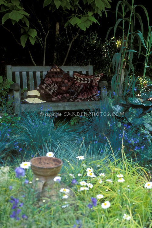 Garden bench in shade, ornamental grasses, flowers, urn 37658