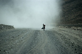 Arequipa, Peru. Quechua woman in traditional dress with a baby on her back in a manta cloth, in a cloud of dust on a dirt road.