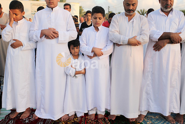 Palestinians attend the morning prayer of the Muslim holiday of the Eid al-Adha on September 12, 2016, in Khan Younis in the southern Gaza strip. Muslims across the world celebrate the annual festival of Eid al-Adha, or the festival of sacrifice, which marks the end of the Hajj pilgrimage to Mecca and commemorates prophet Abraham's readiness to sacrifice his son to show obedience to God. Photo by Ashraf Amra