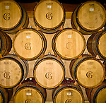 Oak wine barrels stacked in a winery aging the red wine in the Willamette Valley, OR