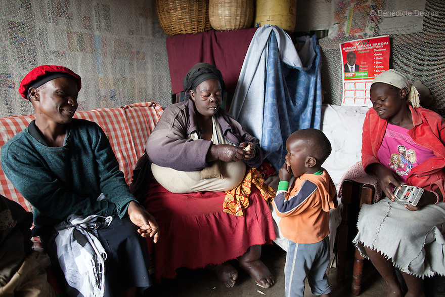 "Susan Kalai aka ""Mama Safi"", a 53 year old Kenyan woman with severe morbid obesity, sits with her family at her home in Kawangware slum in Nairobi, Kenya on December 18, 2012. ""Mama Safi"" lives on less than $1 USD a day, selling vegetables and fried potatoes in the street in front of her house. She has 7 children, the youngest one is 9 years old. She suffers from several obesity-related diseases. She can't walk, has a lot of pain in her legs and back and also has difficulties to breathe. She says ""I was born big. I was always like this. Both my parents and my sister are big too. So for me it's normal. Nothing is wrong with me"". She has no knowledge about obesity and she can't go to the doctor to get treated because she has no money to pay for it. She is afraid to die of a heart attack. Although large parts of Africa are plagued with malnutrition, the continent must now also deal with another problem: obesity. Obesity is fast becoming a serious problem in Kenya and even the poorest are now being affected. Obesity rates are climbing around the world and they are rising faster in developing countries than in developed ones. (Photo by Benedicte Desrus)"