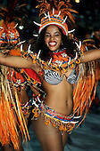 Rio de Janeiro, Brazil. Carnival; woman with big smile in black & white bikini and colourful necklet, waistband and headdress.