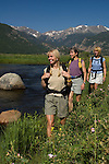 Girlfriends hike near the Big Thompson River at Moraine Park on a clear, blue-sky summer morning in Rocky Mountain National Park, Colorado