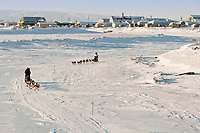 Bruce Linton runs in front of Paul Gebhart on the Unalakleet slough ice after leaving  Unalakleet during the 2010 Iditarod