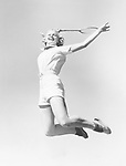 Woman jumping into the air with a tennis racket in her hand