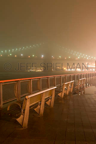 THIS IMAGE IS AVAILABLE EXCLUSIVELY FROM CORBIS.....Please search for image # 42-19640329 on www.corbis.com....Brooklyn Bridge and East River, Viewed from East River Esplanade on a Foggy Night....Lower Manhattan, New York City, New York State, USA