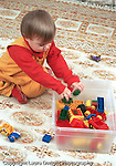 18 month old toddler boy clean up time putting away plastic blocks into container vertical