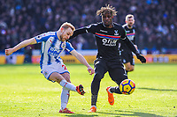 Huddersfield Town's midfielder Alex Pritchard (21) crossed=s with Crystal Palace's midfielder Wilfried Zaha (11) close by during the EPL - Premier League match between Huddersfield Town and Crystal Palace at the John Smith's Stadium, Huddersfield, England on 17 March 2018. Photo by Stephen Buckley / PRiME Media Images.