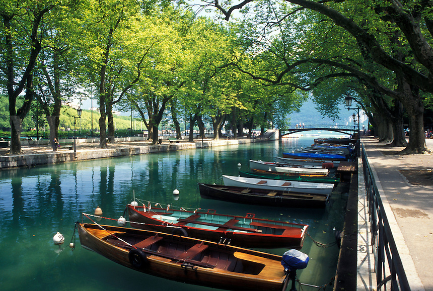 Annecy, France, Haute-Savoie, Rhone-Alpes, Europe, Wooden rowboats docked along the tree-lined Vasse canal on scenic Lake Annecy (Lac d' Annecy) in Annecy.