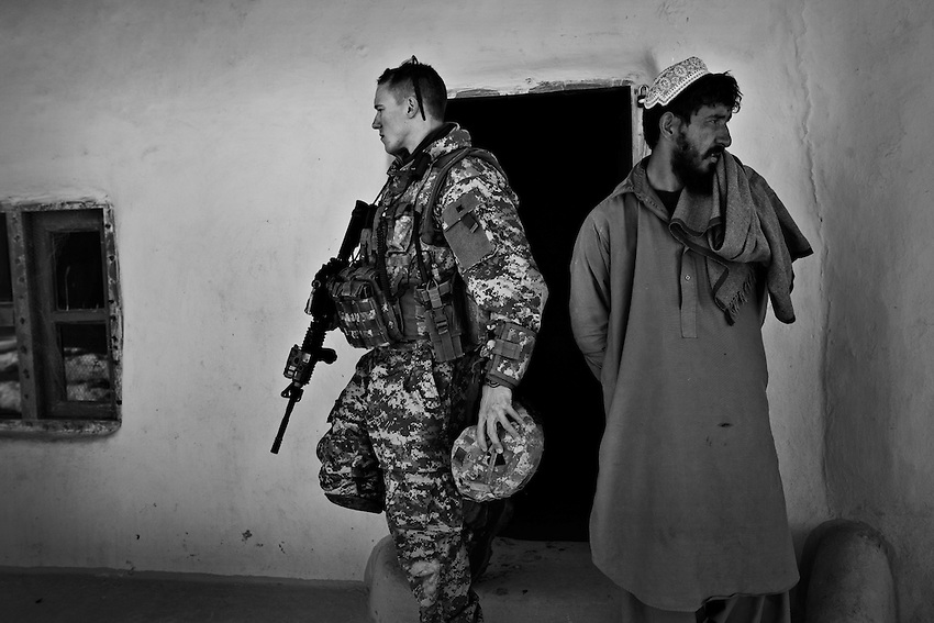 Lt. Randall Waters of Baker Company, 1st Battalion, 506th Infantry, searches an Afghan mans home for weapons during a clearing operation in the village of Ebrahim, Mota Khan District, Paktika Province, Afghanistan, Friday, January 23, 2009.