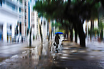 conceptual urban scene with female walking in street with umbrella