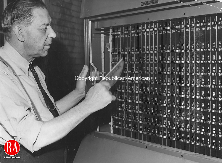 1950 - Peter H. Dunais, voting machine custodian, is shown at work preparing one of the machines for the election on November 7th last.  He is setting the counters back to zero so that they may record the total number of votes cast on the machine.  The rear of the machine is exposed in the picture.  Republican-American Archives.