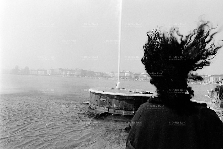 "Switzerland. Geneva. Woman's dark long curly hair blowing in the wind and the famous water fountain "" Jet d'eau "" on the lake of Geneva. © 1988 Didier Ruef"