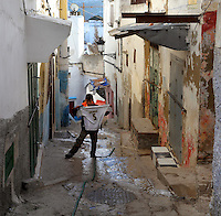 A boy holding a Zidane football top in a steep narrow street in the medina or old town of Tetouan on the slopes of Jbel Dersa in the Rif Mountains of Northern Morocco. Tetouan was of particular importance in the Islamic period from the 8th century, when it served as the main point of contact between Morocco and Andalusia. After the Reconquest, the town was rebuilt by Andalusian refugees who had been expelled by the Spanish. The medina of Tetouan dates to the 16th century and was declared a UNESCO World Heritage Site in 1997. Picture by Manuel Cohen