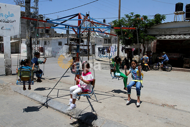 Palestinian children play on a swing in Rafah in the southern Gaza strip on July 18, 2015, on the second day of Eid al-Fitr holiday which marks the end of the Muslim holy month of Ramadan. Photo by Abed Rahim Khatib