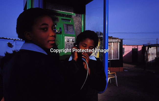 dicommu00151.Communication Telephones. Schoolgirls talk on a puplic telephone early in the morning before going to school on November 5, 2003 in Site C, Khayelitsha outside Cape Town, South Africa..©Per-Anders Pettersson/iAfrika Photos