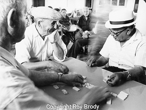 Elderly men playing dominoes in a recreation club.