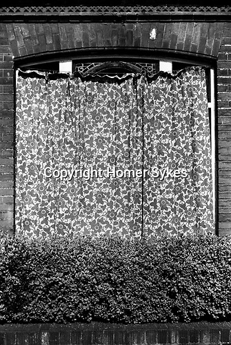 Exterior of house, curtain drawn across the window as protection against the sun. London 1971