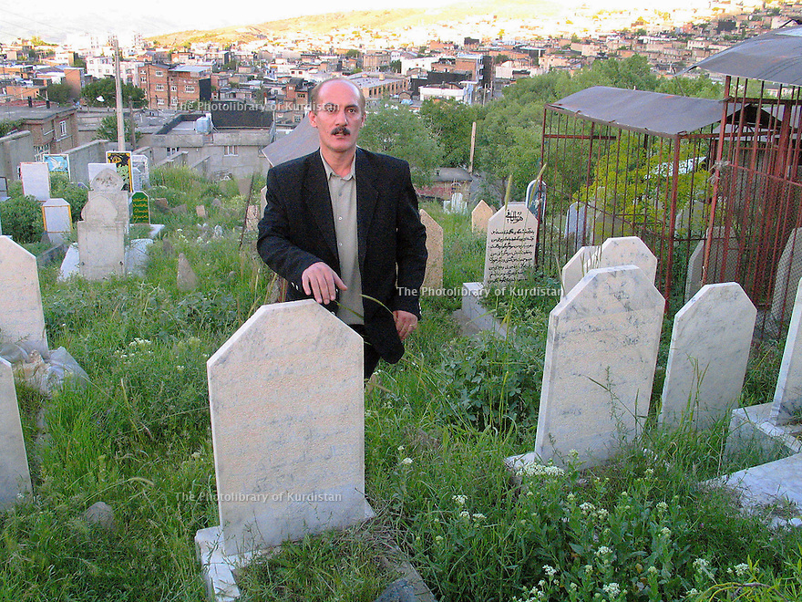 Iran 2004.A Sardacht, ville bombardée chimiquement par les Irakiens, un habitant montre au cimetiere les tombes de parents victimes des gaz chimiques.<br /> Iran 2004.In Sardacht, Kurdish town, bombed with chemical weapons by the Iraqis, the gravestones of the victims  <br /> ئیران سالی 2004 ، سه رده شت ، شاری کیمیاویی کراو له لای عیراقییه کان . یه کیک له دانشتووانی سه رده شت گوری دایک و باوکی  نیشان ده دات که قوربانی گازی .شیمیاوی بوونه