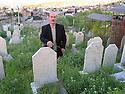 Iran 2004.A Sardacht, ville bombard&eacute;e chimiquement par les Irakiens, un habitant montre au cimetiere les tombes de parents victimes des gaz chimiques.Iran 2004.In Sardacht, Kurdish town, bombed with chemical weapons by the Iraqis, the gravestones of the victims  <br /> ئیران سالی 2004 ، سه رده شت ، شاری کیمیاویی کراو له لای عیراقییه کان . یه کیک له دانشتووانی سه رده شت گوری دایک و باوکی  نیشان ده دات که قوربانی گازی .شیمیاوی بوونه
