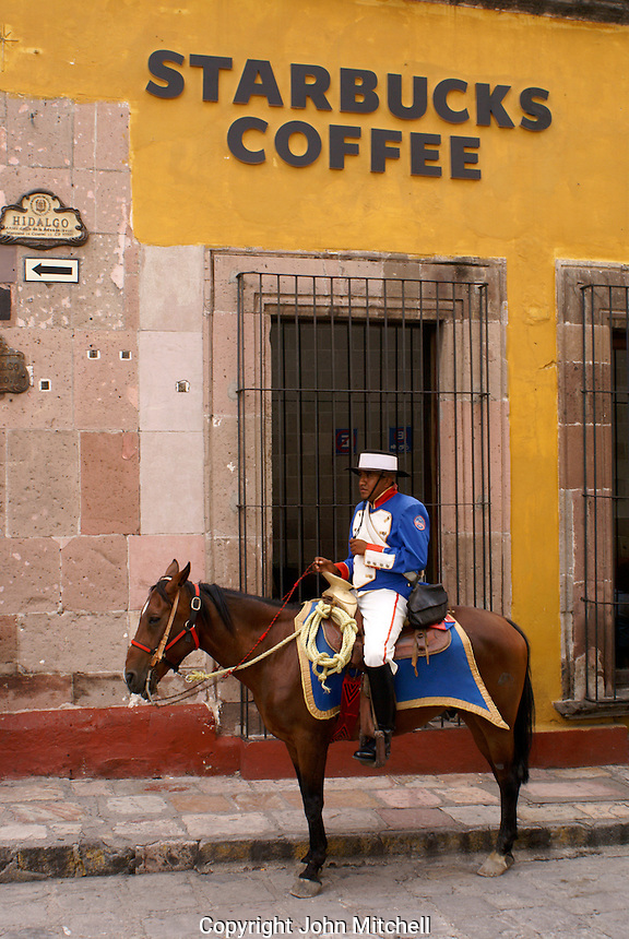 Policeman in traditional Spanish costume on horseback next to Starbucks Coffee shop in San Miguel de Allende, Mexico. San Miguel de Allende was made a UNESCO World Heritage site in 2008.