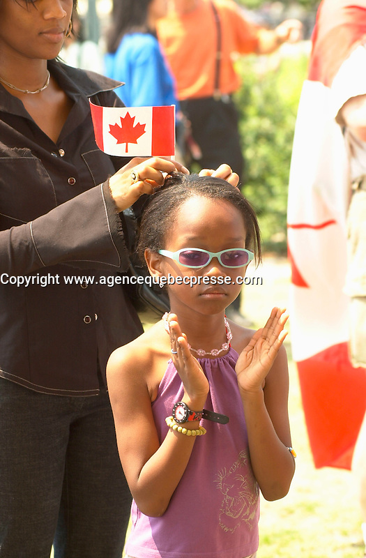 July 1 2002, Montreal, Quebec, Canada<br /> <br /> An African mother put a Canadian flag in her 7 year old daughter's hair before the receive their Canadian citizenship, in an official ceremony, July 1st 2001, in the Old-Port of Montreal. No Model Release <br /> <br /> Mandatory Credit: Photo by Pierre Roussel- Images Distribution. (&copy;) Copyright 2002 by Pierre Roussel <br /> <br /> NOTE l Nikon D-1 jpeg opened with Qimage icc profile, saved in Adobe 1998 RGB. Original file size available in TIFF file.