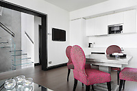 Bright pink velvet chairs with a mottled  silver/grey pattern stand out against the monochrome tones of the kitchen/dining area