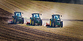 Three John Deere tractors rotary hoe oat stuble at Bombay in readiness for autumn planting of a broccoli crop. Franklin district, Auckland region, New Zealand.