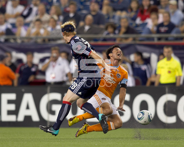 Houston Dynamo forward Brian Ching (25) goes down after collision with New England Revolution defender Pat Phelan (28). The New England Revolution defeated Houston Dynamo, 1-0, at Gillette Stadium on August 14, 2010.