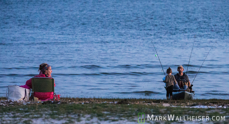A mother and her two children enjoy Shell Point Beach as her husband arrives from fishing in the north Florida panhandle town of Crawfordville and chat the sunset away.