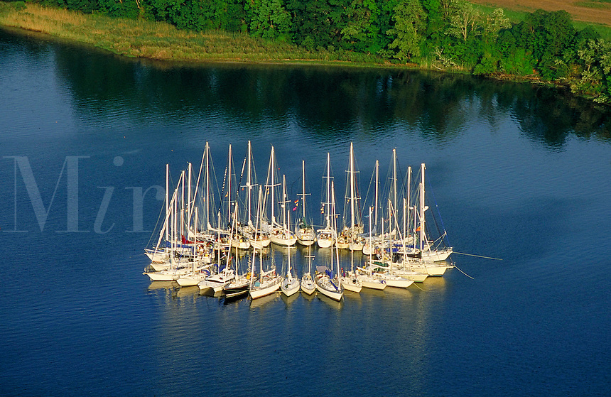 Aerial, 30 sailboats rafted up in a circle with blue water and shoreline behind, boats, boat formations. Chesapeake Bay Maryland USA.