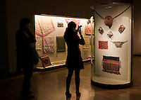 Visitors look at a textiles collection on display in glass cases at the Shanghai Museum, China