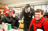 Wednesday March 7, 2007   ----  Aaron Burmeister, Race Judge Mark Nordman, and Ramy Brooks take in a laugh while hanging out inside the community center at Takotna.
