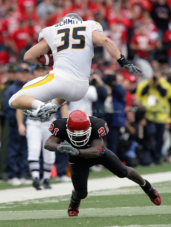 Rutgers # 21 (lower)- Devin McCourty misses the tackle of West Virginia's # 35- (top)- Owen Schimitt as he leaps over McCourty for 1st down yardage, as Rutgers is beaten by West Virginia 31-3 on Sat.Oct. 27,2007.<br />