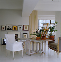 Photographs are displayed on shelves around the living area and the gate-legged table is filled with orchid plants in terracotta pots
