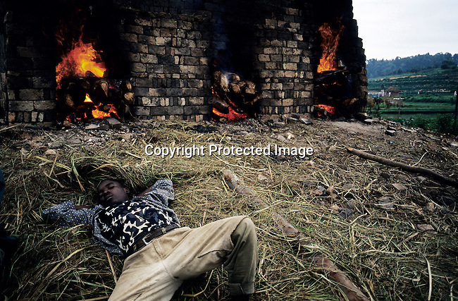 A brick-making factory worker takes a nap early in the morning as he has worked the whole night keeping a fire alight on February 14, 2003. About 100.000 prisoners accused of the genocide are still in prisons nine years later. About 800.000 mainly Tutsis and moderate Hutus were killed in about one hundred days in 1994. Rwanda is currently trying to cope with these huge problems and some prisoners that have confessed to crimes can be tried in village trials. (Photo: Per-Anders Pettersson)