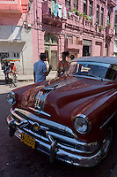 stret scene with people talking next to a red oldtimer, american car, in front of a pink building,  Havana, Cuba